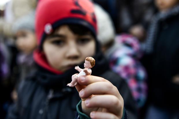 Un ragazzo con la statuetta di Gesù Bambino in mano