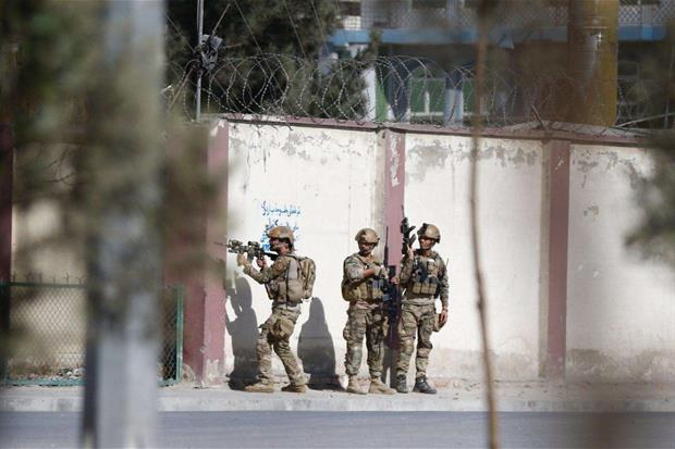 Forze di sicurezza afghane appostate all'ingresso di Shamshad tv durante l'attacco (Ansa)