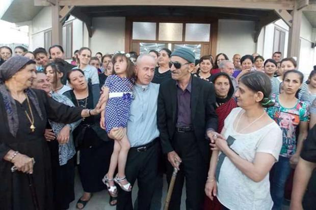 Cristina in braccio a padre Jalal Yako, con a destra i genitori della bimba