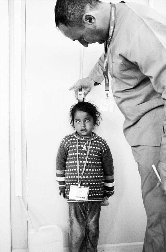 Un medico di EMERGENCY visita una bambina nel Centro Sanitario del campo di Ashti (© Giles Duley)