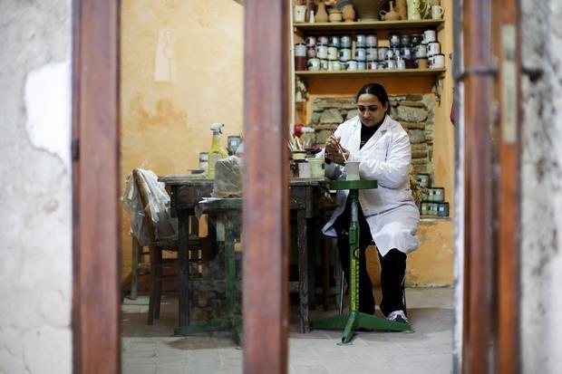 Una migrante pakistana lavora la ceramica in una bottega del centro storico di Riace, prima abbandonata. I profughi accolti in paese hanno imparato i vecchi mestieri dagli abitanti locali e ne portano avanti la tradizione