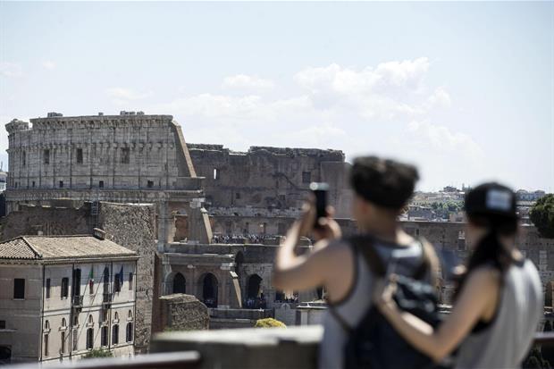 Due turisti fotografano il Colosseo dal Colle Palatino (Ansa)