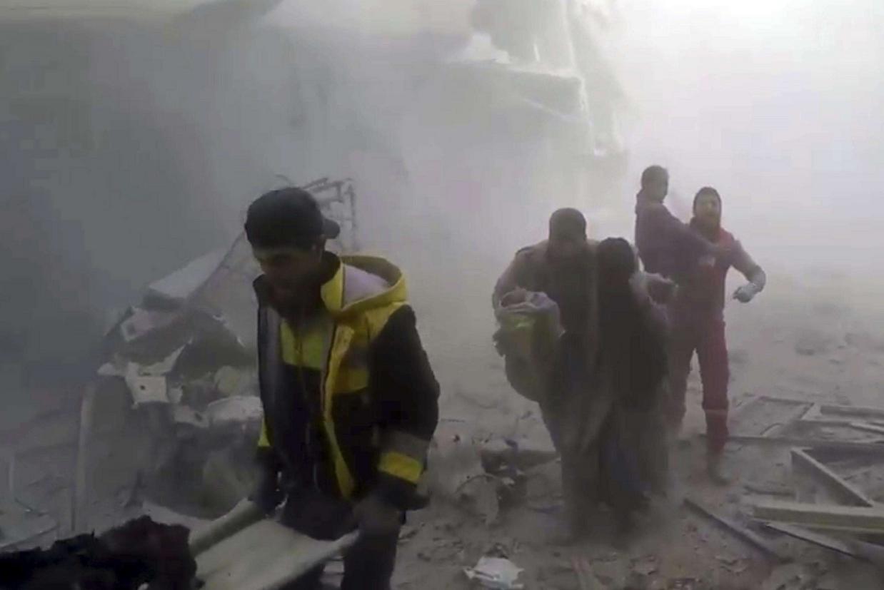 Il Gruppo di difesa civile siriano (gli 'Elmetti bianchi') aiuta i residenti a mettersi in salvo durante i bombardamenti su Ghouta, il martoriato sobborgo di Damasco (Ansa)
