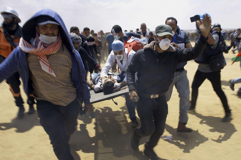 Medici e dimostranti trasportano un giovane ferito a est di Khan Younis, nella Striscia di Gaza (Ansa)