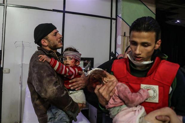 Foto rilasciata dal gruppo anti-governativo siriano Ghouta Media Center, mostra due bambini siriani feriti durante gli attacchi aerei a Ghouta, alla periferia di Damasco (Ansa)