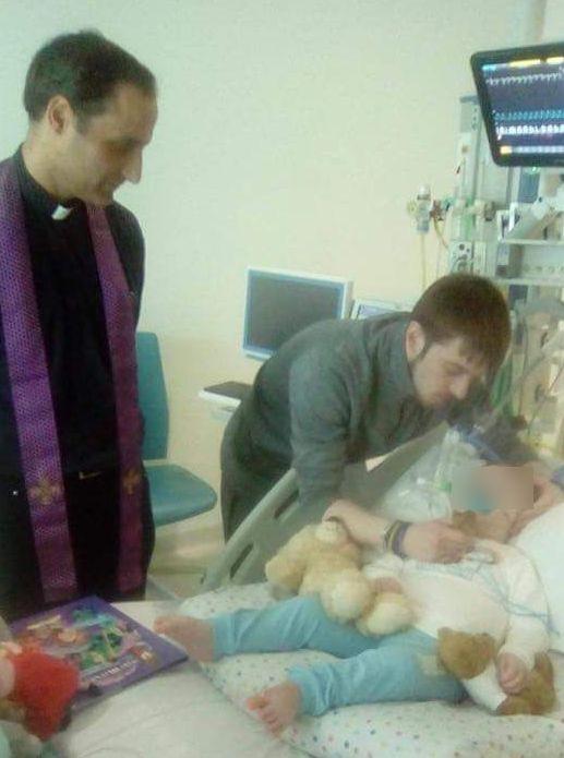 Alfie con il padre e il sacerdote in ospedale