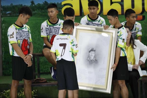Il ringraziamento. I ragazzi mostrano l'immagine di Saman Gunan, il sub morto per salvarli (Ansa)