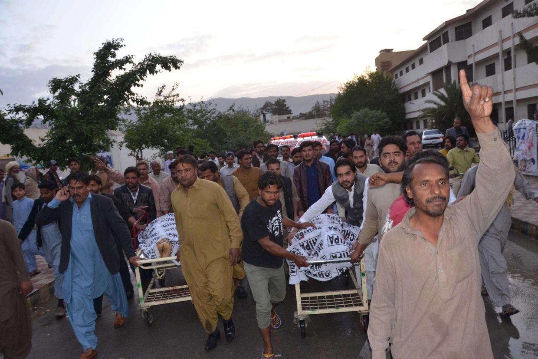Cristiani di Quetta scandiscono slogan di protesta mentre trasportano i corpi dei due cristiani uccisi (Ansa)
