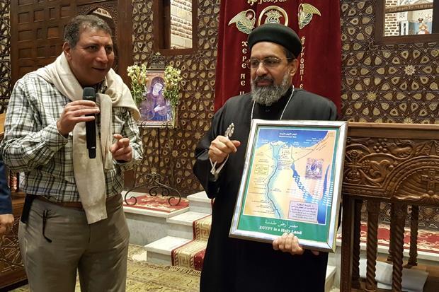 Un sacerdote copto con la carta che illustra la fuga in Egitto della Santa Famiglia (foto Gambassi)