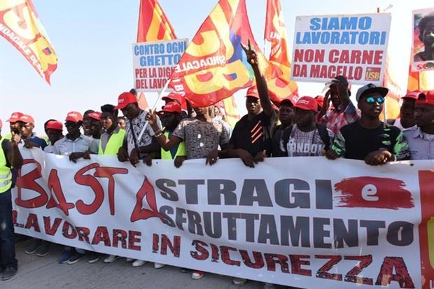 Lavoratori migranti protestano durante la manifestazione organizzata dai sindacati di base (Ansa)
