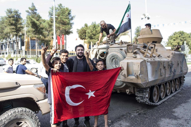 Alcuni civili con la bandiera della Turchia durante l'attacco contro i curdi in Siria (foto Ansa)