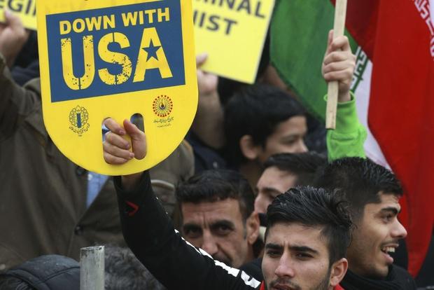 Manifestante mostra poster antiamericano durante i festeggiamenti del regime (AP)
