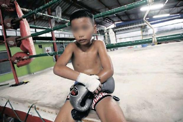 Un bambino di 10 anni si leva i guantoni dopo un incontro a Bangkok