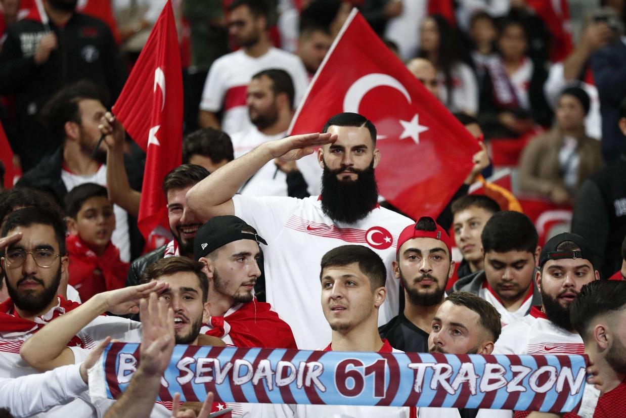 Tifosi turchi fanno il saluto militare prima dell'inizio della partita Francia-Turchia, a Parigi (Ansa)