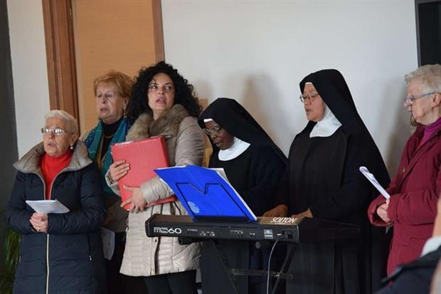 Due benedettine cantano con il coro