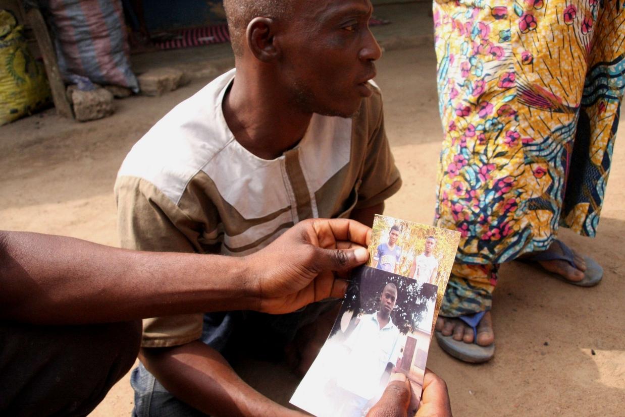 Il fratello poliomelitico di Tamimou Derman con le foto di qualche anno prima del migrante morto e un altro fratello (foto M. Fraschini Koffi)