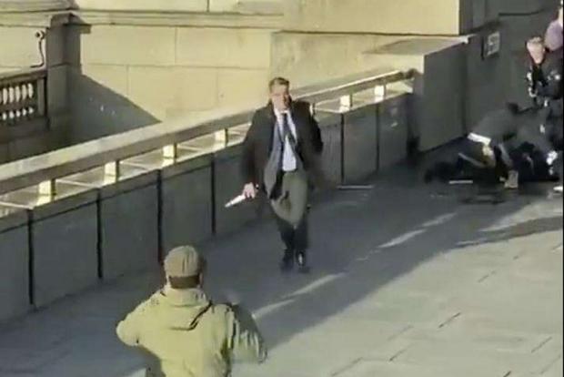 Gli agenti immobilizzano l'accoltellatore, dopo che era stato disarmato da alcuni passanti (Ansa)