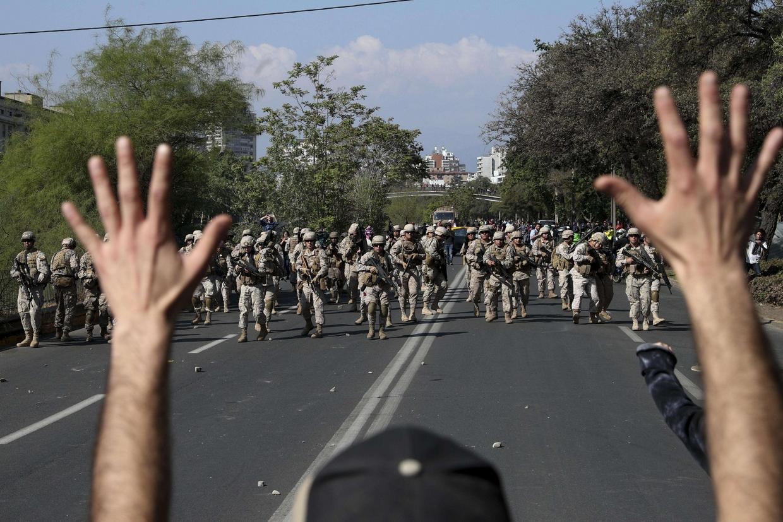 Un manifestante alza le mani in segno di resa davanti ai militari a Santiago del Cile (Ansa)