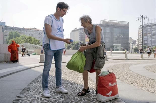 Un giovane volontario del Progetto Arca consegna un succo di frutta fresco a un senza fissa dimora nel centro di Milano, ieri ancora tra le città da bollino rosso per le temperature da record. L'afa, e la mancanza di ricoveri attrezzati d'estate, mettono a rischio i clochard