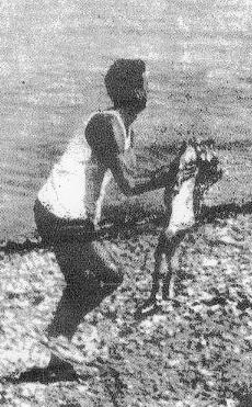 Una celebre immagine di una piccola vittima raccolta sulla spiaggia di Vergarolla dopo l'attentato