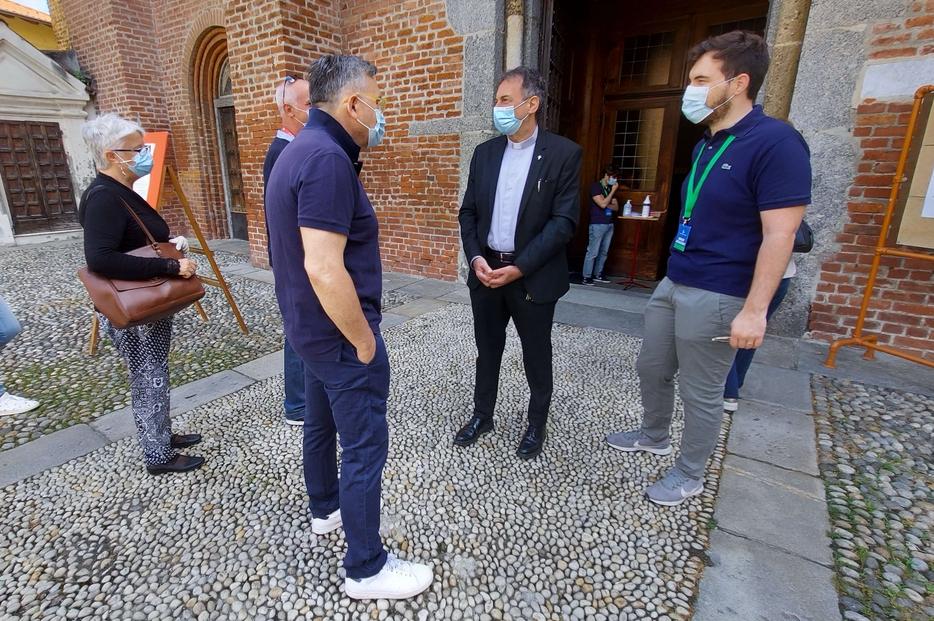 Don Franco Amati mentre domenica dà il benvenuto ai fedeli di fronte alla chiesa di Crescenzago a Milano