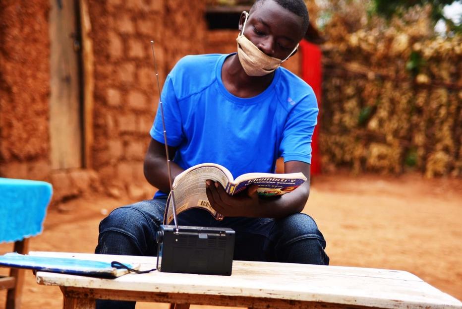 Mascherina, didattica a distanza (via radio) e lezione all'aperto per questo studente ruandese