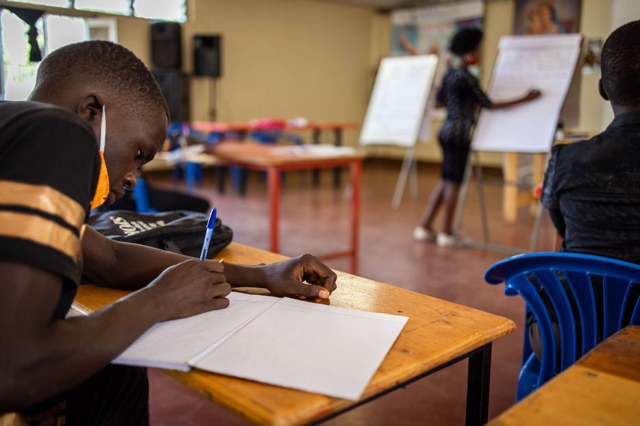 Uno studente in aula in Uganda, nel rispetto delle misure anti Covid
