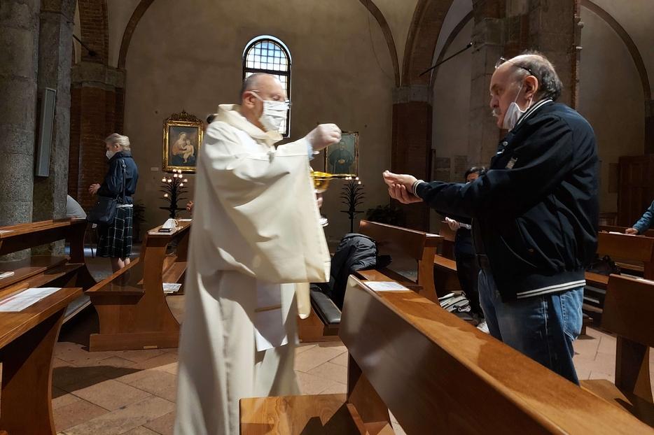 La Comunione durante la prima Messa 'pubblica' nella Basilica di San Babila a Milano