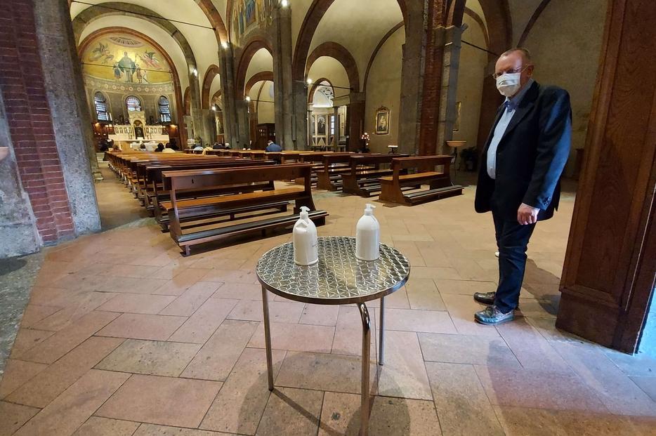 Don Magnani accoglie i fedeli con il gel per la prima Messa 'pubblica' nella Basilica di San Babila a Milano