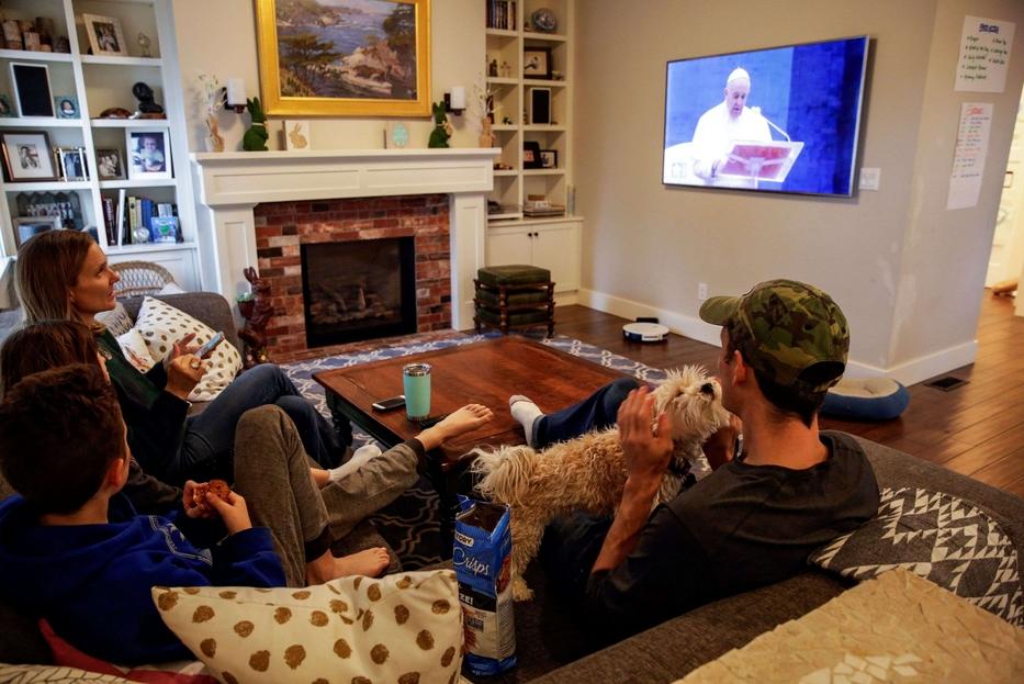 Una famiglia mentre segue in diretta tv la preghiera e la benedizione Urbi et Orbi di papa Francesco