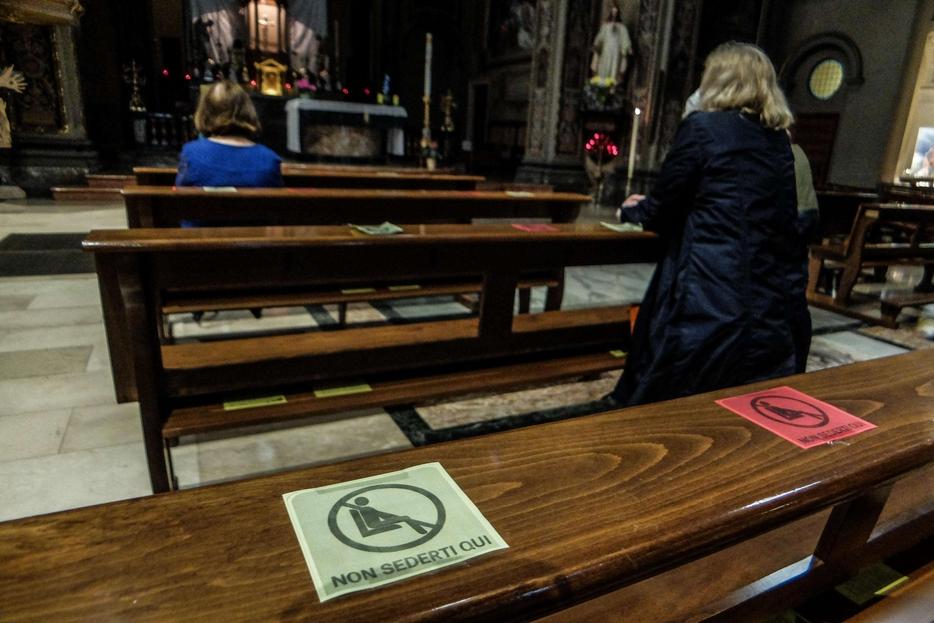 I cartelli sulle panche di una chiesa per mantenere le distanze di sicurezza