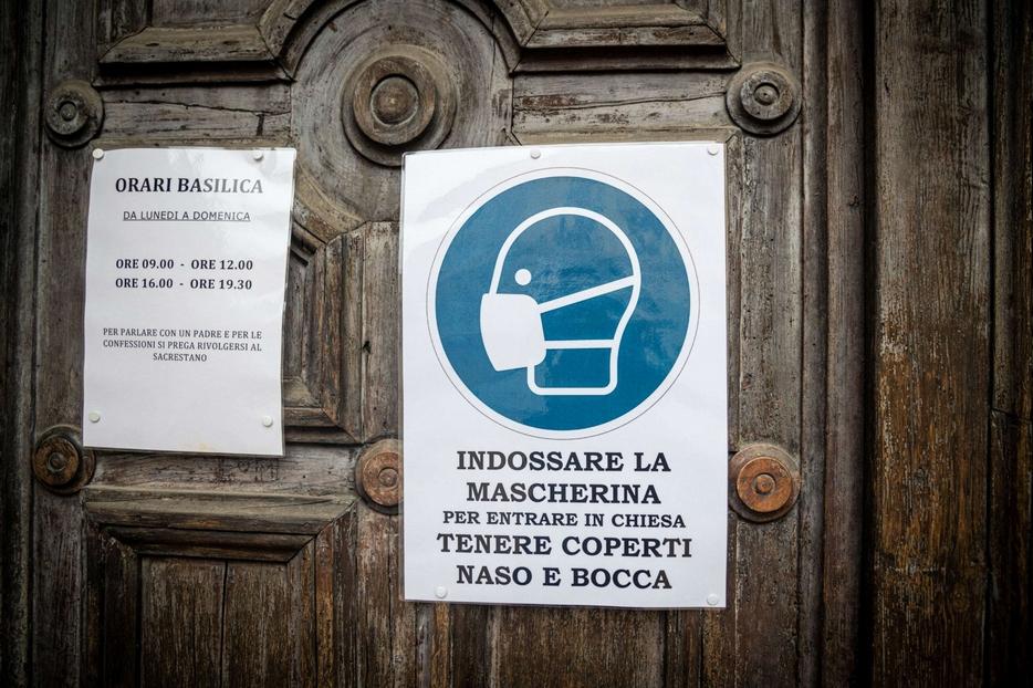 All'ingresso di una chiesa il cartello che indica l'obbligo della mascherina