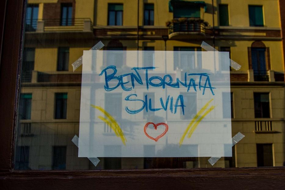 Un cartello appeso sul portone del condominio dove abita la cooperante, a Milano
