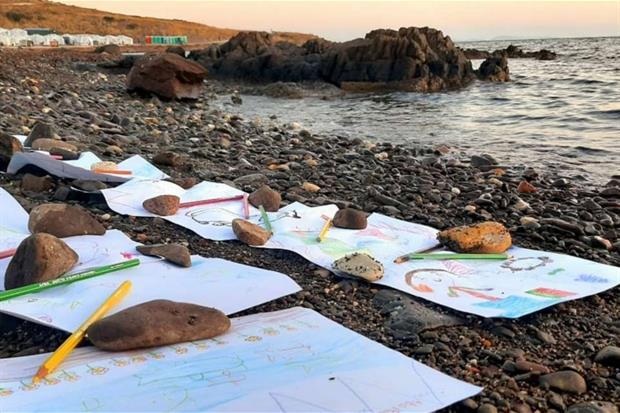 sassi e disegni lasciati in riva al mare, da dove molti di loro sono sbarcati'