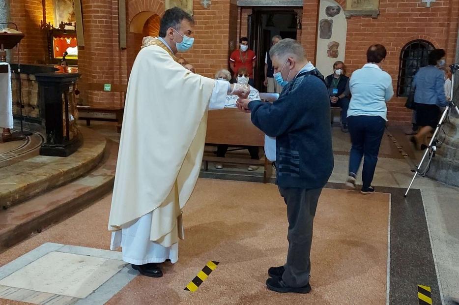 Don Franco Amati, parroco di Santa Maria Rossa nella periferia di Milano, è stato in fin di vita per il Covid. Nella foto mentre dà la Comunione a un fedele, contagiato e ormai guarito - Avvenire