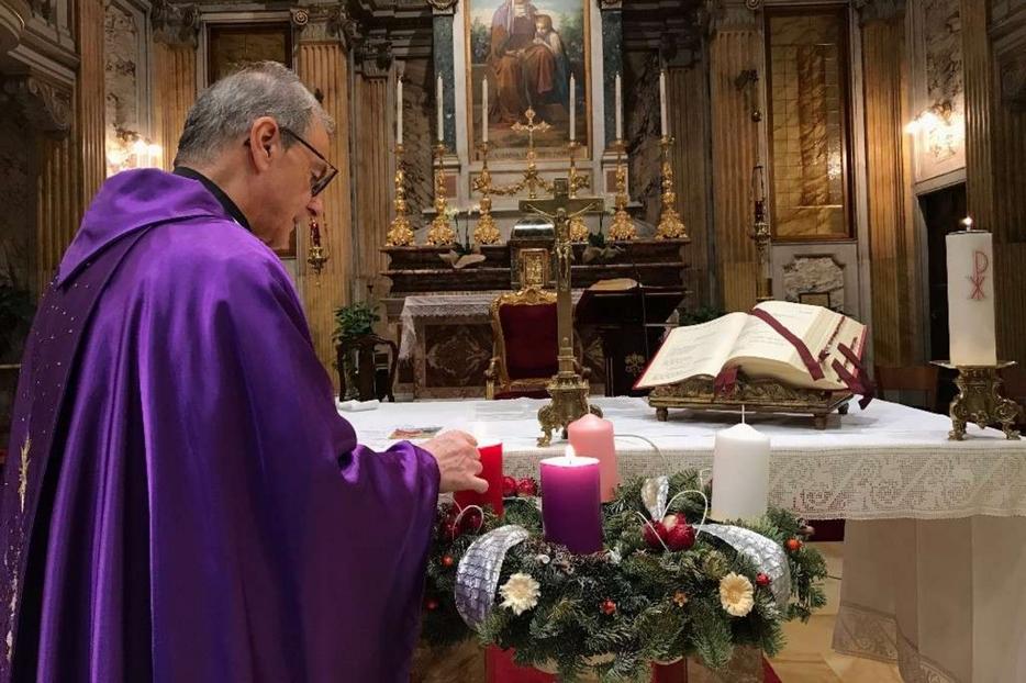 Un sacerdote accende le candele della corona d'Avvento