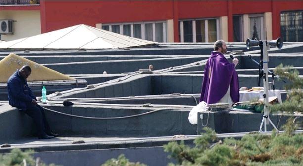 Padre Raffaele sul tetto della chiesa. A sinistra, il viceparroco padre Jean Kambou, della Costa d'Avorio