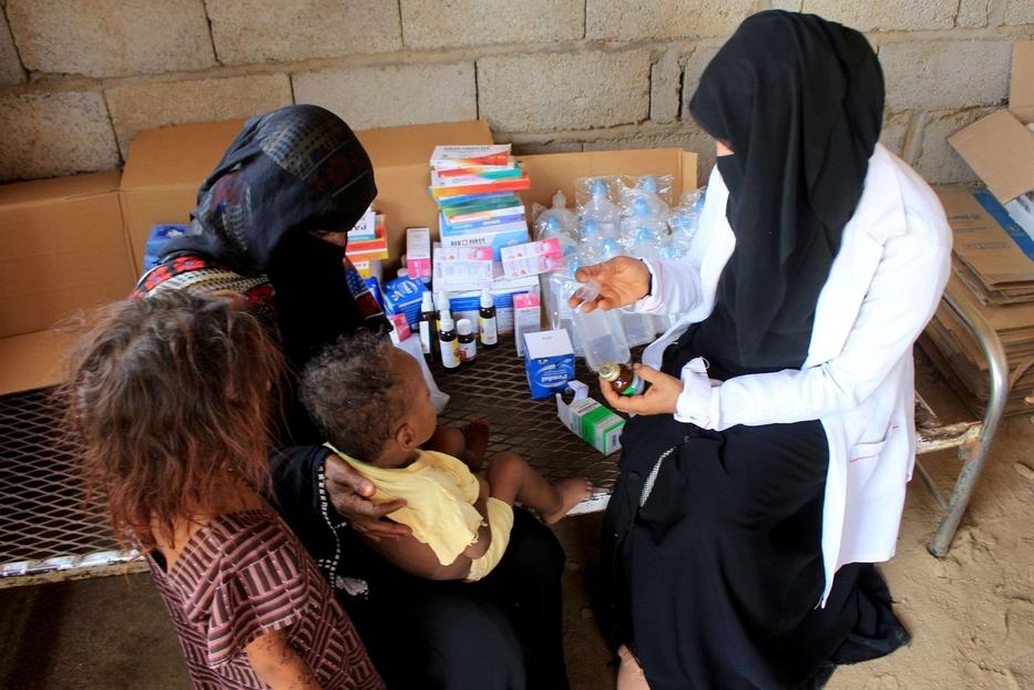 Mahmoud controlla un medicinale per un bambino prima di consegnarlo alla madre