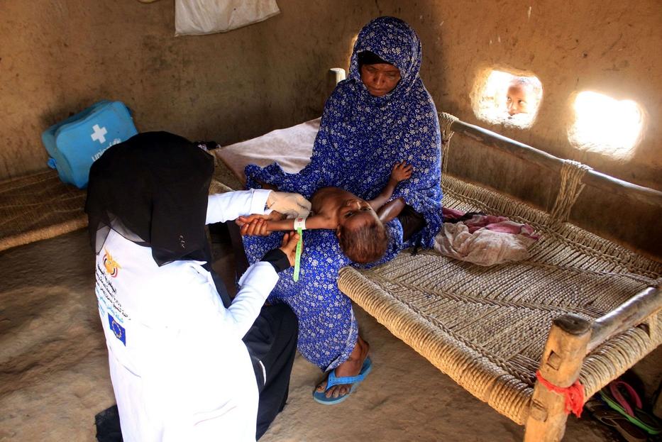 Mahmoud misura il braccio di una bambina per valutarne lo stato nutrizionale