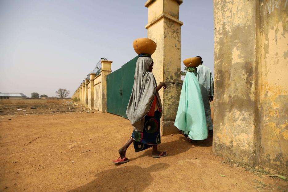 Due donne entrano dal cancello della scuola dove 317 ragazze sono state rapite