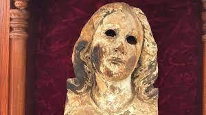 La testa della statua della Vergine ritrovata tra le macerie