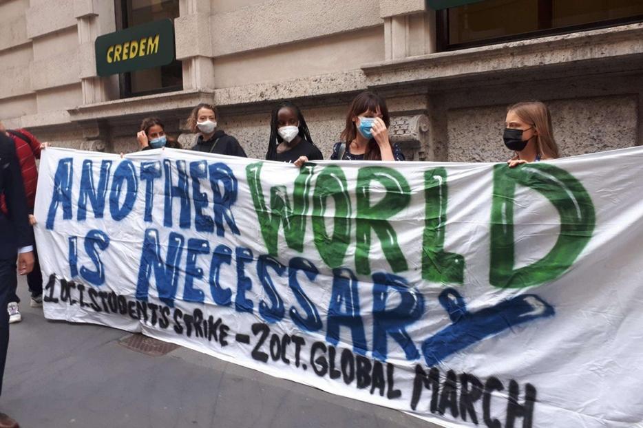 Uno striscione dei giovani ambientalisti davanti alla Prefettura. Da destra, le attiviste Thunberg, Comparelli e Nakate
