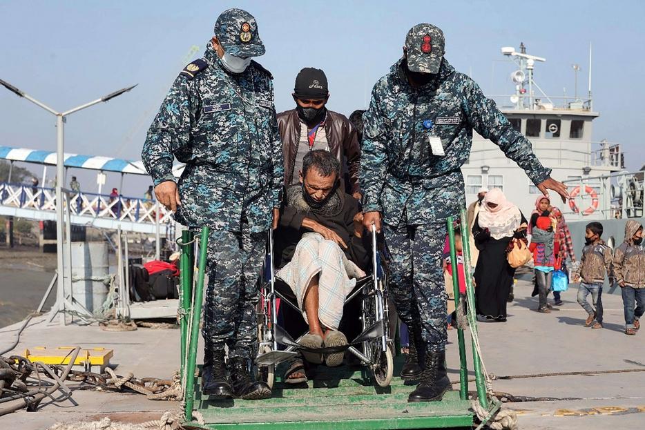 Un anziano invalido aiutato a imbarcarsi nel porto di Chittagong