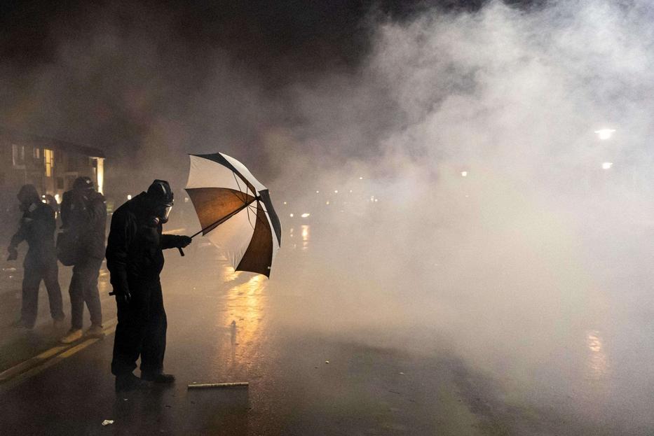 Un manifestante si ripara dai gas lacrimogeni sparati dalla polizia