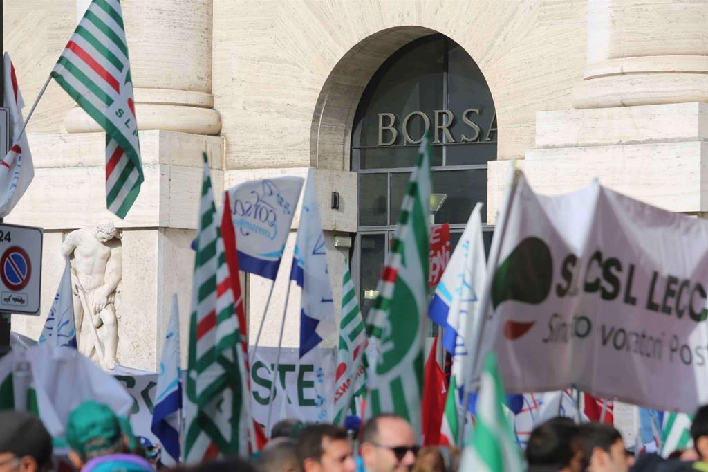Le bandiere dei postali davanti alla Borsa di Milano (Fotogramma) -