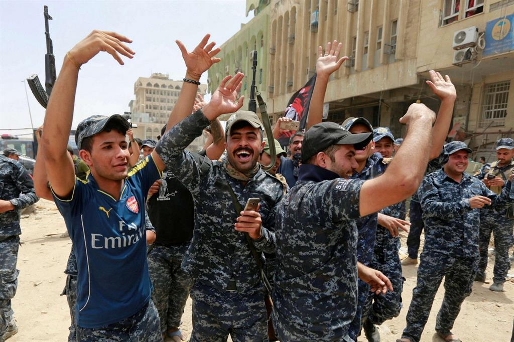 Agenti della polizia irachena esultano nella città vecchia di Mosul (Reuters)