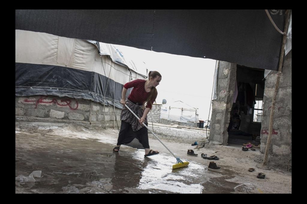 Una giovane ragazza Yazida aiuta la madre nei lavori di casa. -
