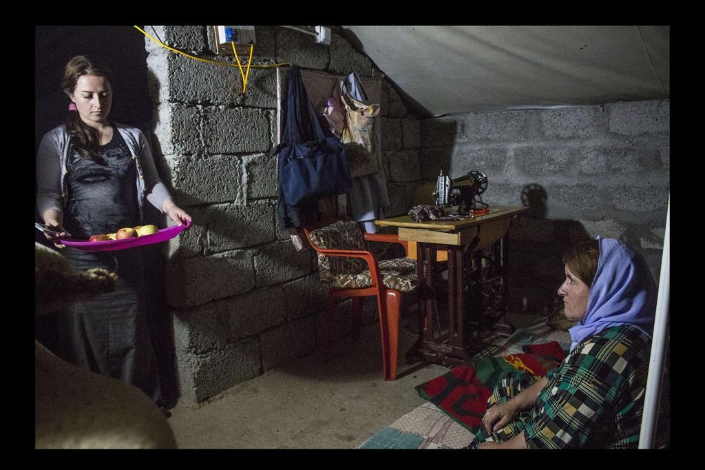 Ragazza Yazida del campo porta la frutta dopo aver cenato con la madre. -