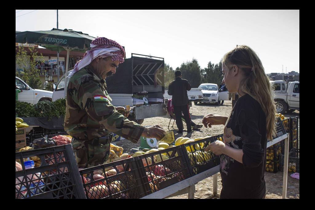 """Hina Qasim Mahmoud, tredici anni. É una studentessa di prima media e divide il suo tempo tra studio e lavoro. La mattino vende verdure al mercatp per aiutare la sua famiglia. È l'unica ragazza Yazida che lavora al mercato. Suo padre è un Peshmerga: """"colui che affronta la morte"""". -"""