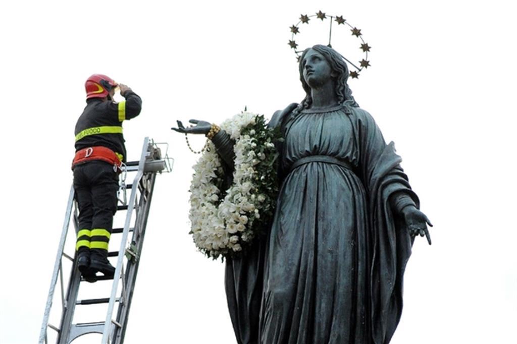 Un vigile del fuoco omaggia la statua mariana in Piazza di Spagna